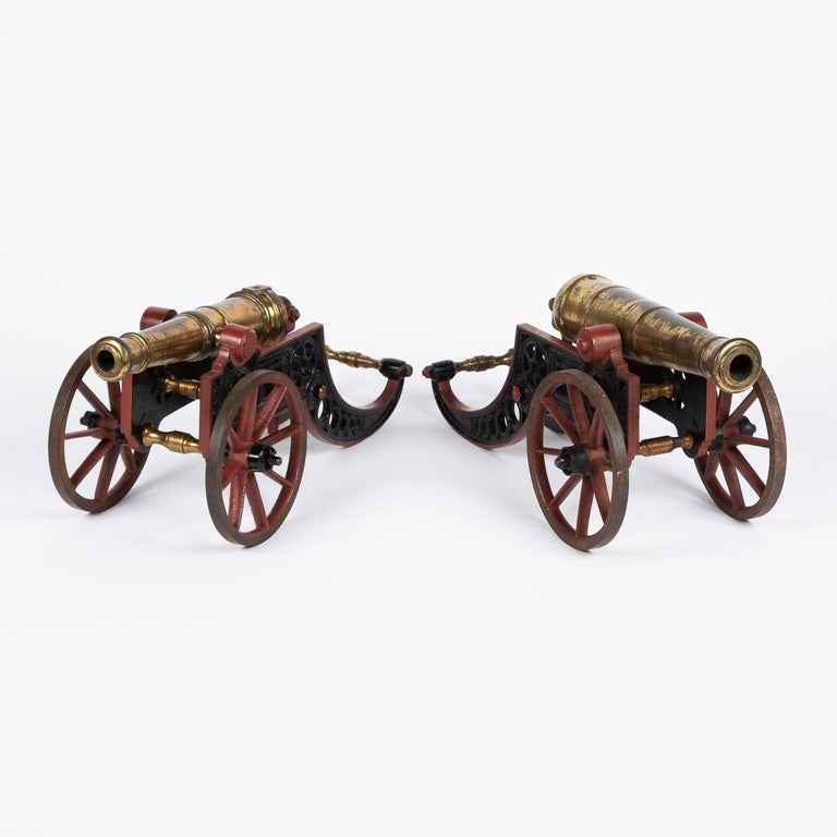 Two bronze table cannon on painted ironwork carriages, with adjustable elevation, English, circa 1900.  Each cannon barrel is of a different size, the larger is 11 1/2