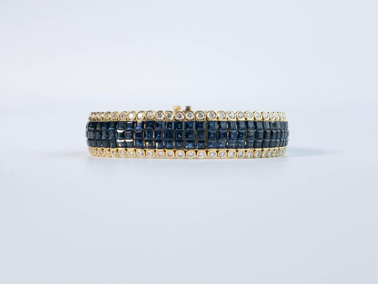 A fine blue sapphire and diamond bracelet set in yellow gold.  This lovely piece displays 204 pieces of square cut natural blue sapphires from Thailand in three rows of invisible setting and accented with 136 bezel set round white diamonds.  Blue