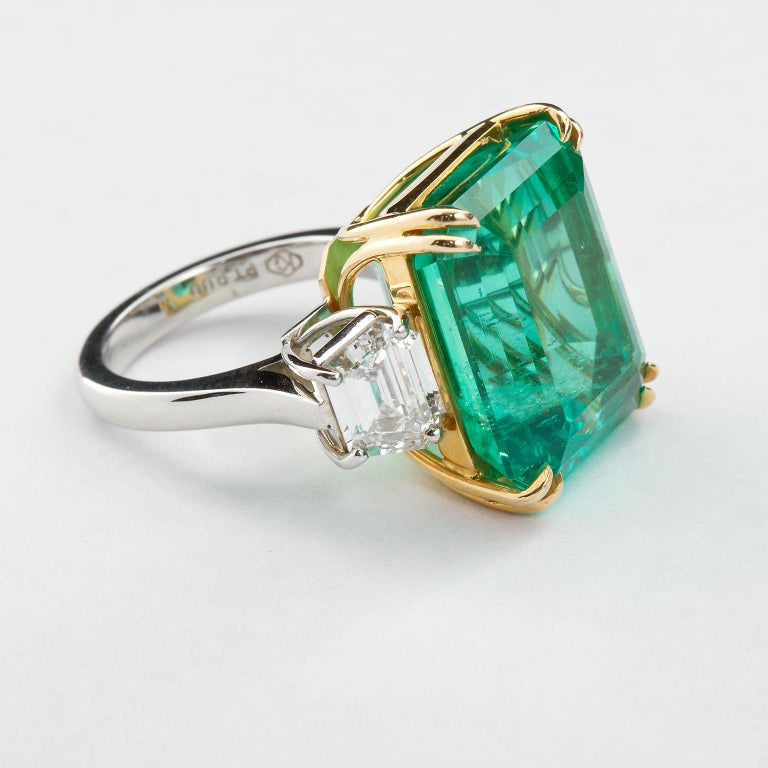 A remarkable fine Colombian emerald set in an 18k and platinum two diamond side-stone ring. The 22.54 carat emerald shows very good color being deep green and highly transparent. Slight threading towards the bottom and side of the table. Set between