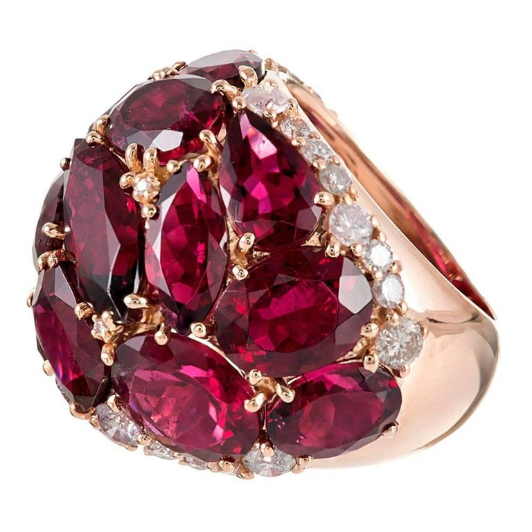 Warm hues of magenta rubellite are peppered with brilliant white diamonds atop a polished mounting of 18 karat rose gold. The ring boasts playfulness and mid-century-inspired character in addition to its 20 carats of tourmaline and .70 carats of