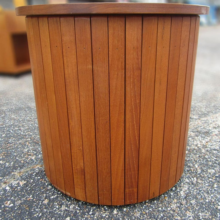 This is a vintage wooden drum side table, finished in teak with a removable top. This drum is great for display or as a small side table. This would look great in any modern home or office for storage and decorative purposes.