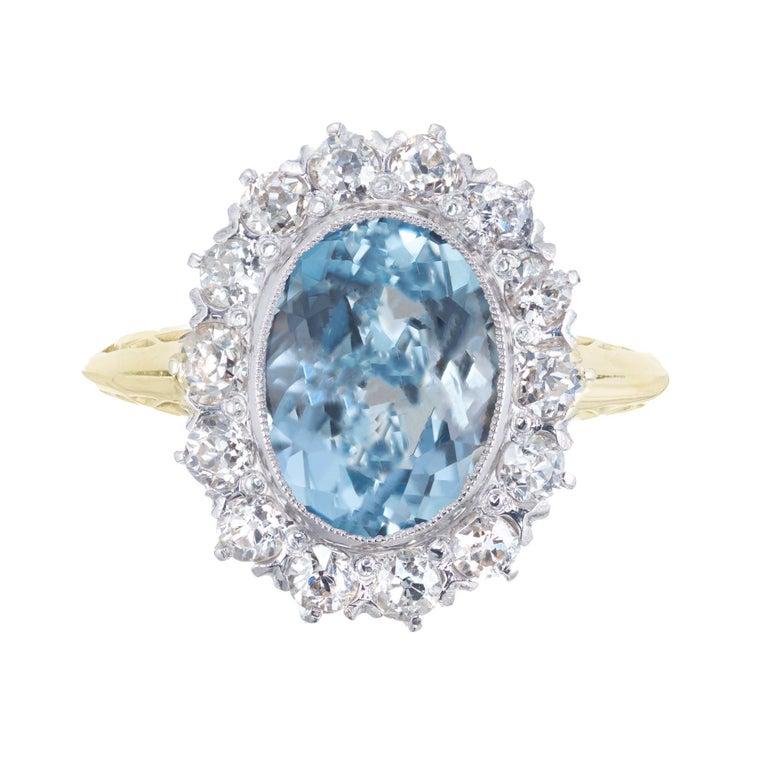 1930's Art Deco Oval aquamarine center stone with a halo of 14 old European cut accent diamonds in a 14k yellow and white gold setting.   1 oval blue Aquamarine, approx. 2.00ct 14 old European cut diamonds I-J SI-2, approx. .42cts Size 4.75 and