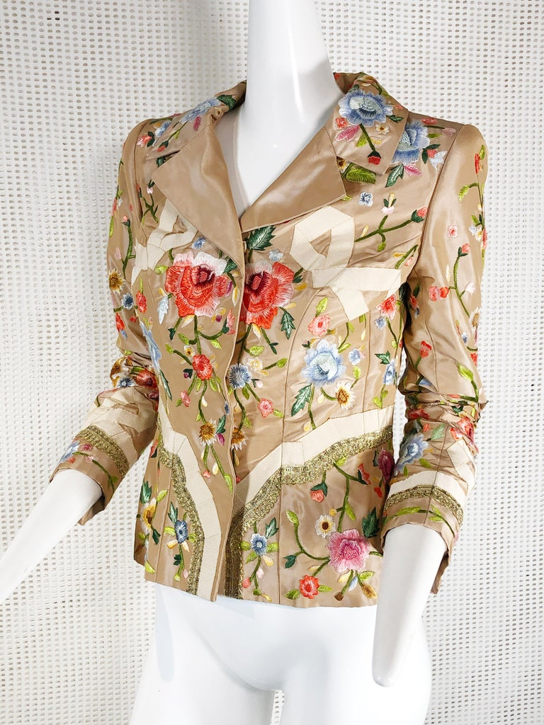 This feminine 2000 Oscar de la Renta jacket features gorgeous polychrome embroidered roses and petersham French bows with metallic braid at sleeves and hip. Front snap closure. Fits a modern size 4.