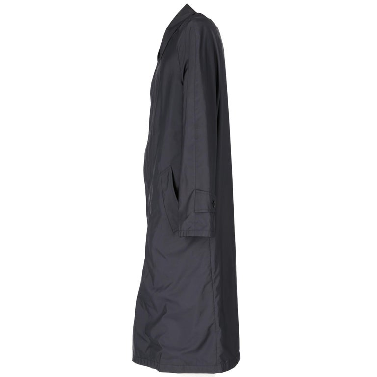 Aquascutum blue long up to the knee  raincoat, with classic collar, long raglan sleeves, frontal English fastening with buttons, two front welt pockets and slit on the back. Inside there is a rectangle of vichy fabric surrounded by a zip that allows