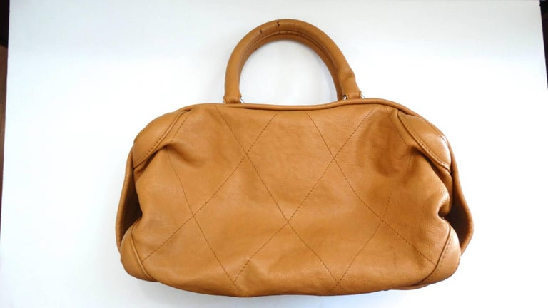 The most adorable tan top handle bag from 2000s Chanel! Made of a soft tan leather with detailed quilted stitching. Slouchy, hobo style silhouette with top handle construction. Silver metal zipper across the top with large Chanel CC medallion zipper