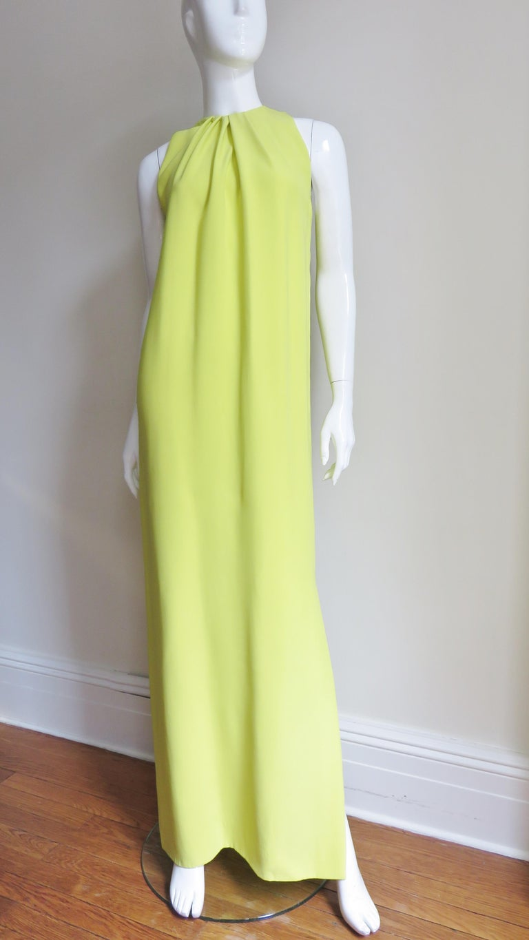 A beautiful bright citron lemon lime silk gown from Christian Dior.  It has a crew neckline with tucks around it's circumference opening to create fullness to the hem- simple and elegant.  The skirt portion is straight and has a side slit.  It is