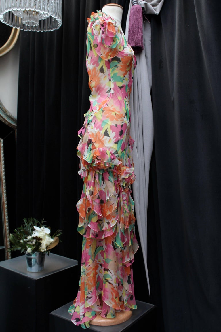 CHRISTIAN DIOR (Made in France) Lovely long cocktail dress made of silk with floral pattern print in pink, green, yellow and orange tones. The tight-fitting dress is decorated at its short sleeves and bottom with several flounces, which gives it a