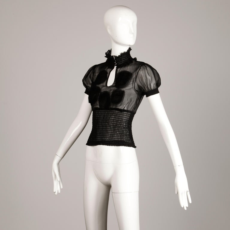 Costume National short sleeve sheer black top or blouse with rhinestone buttons and elastic smocking. Embroidered detail and keyhole front. Front button closure. Waistband, sleeve cuffs and neckline are stretchy. The marked size is 40 and this fits