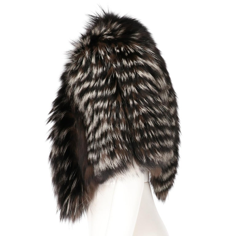 Gianfranco Ferrè real silver fox fur cape short to the waist, with black and white inlay, with padded shoulders, elastics and hooks for the arms, lined in silk, front closure with hook and chain.  This item belongs to an original vintage stock: it