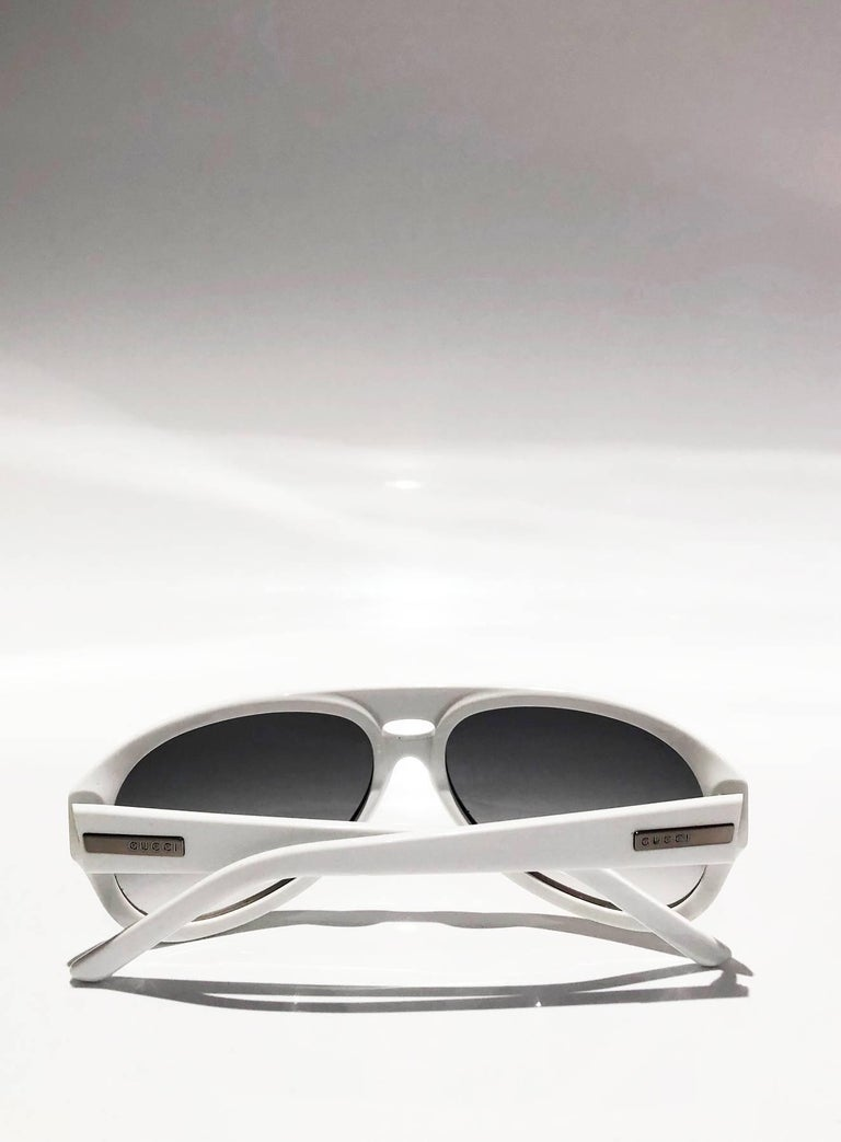 FREE UK and WORLDWIDE DELIVERY   Gucci Aviator Sunglasses featuring Sporty design, white plastic frame plastic core and engraved Gucci logo, grey/purple shaded lens, Made in Italy, 100% UVA/UVB protection Size: Medium, width: 5.7 in Condition: