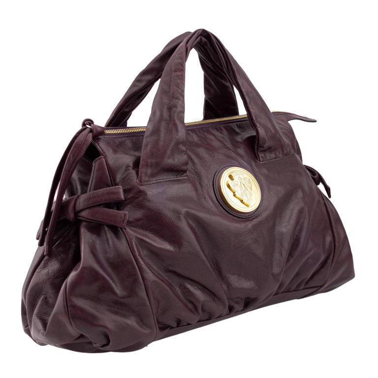 Gucci slouchy top handle bag from the early 2000's Hysteria collection. Maroon leather with contrasting gold tone hardware. Leather bow details on both sides, heavy zipper across the top with long matching leather pull and large round Gucci crest.
