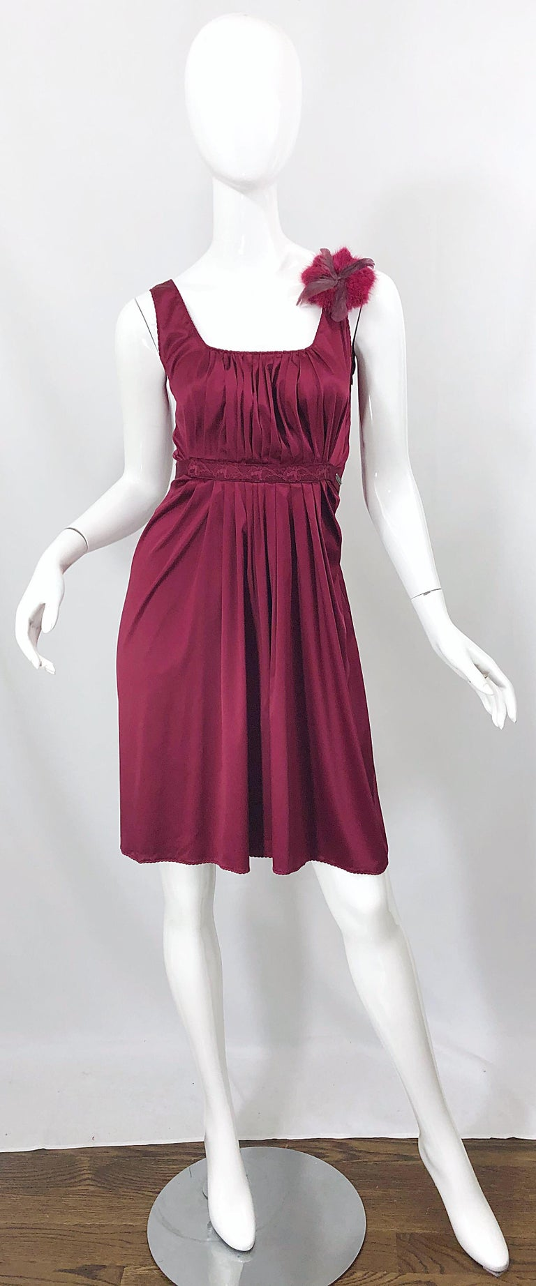 Beautiful early 2000s JOHN GALLIANO burgundy / maroon / merlot silk sleeveless dress with removable feather brooch! Pleated bodice with a tie at back waistband to adjust waist size. Hidden zipper up the side with hook-and-eye closure. Feather brooch
