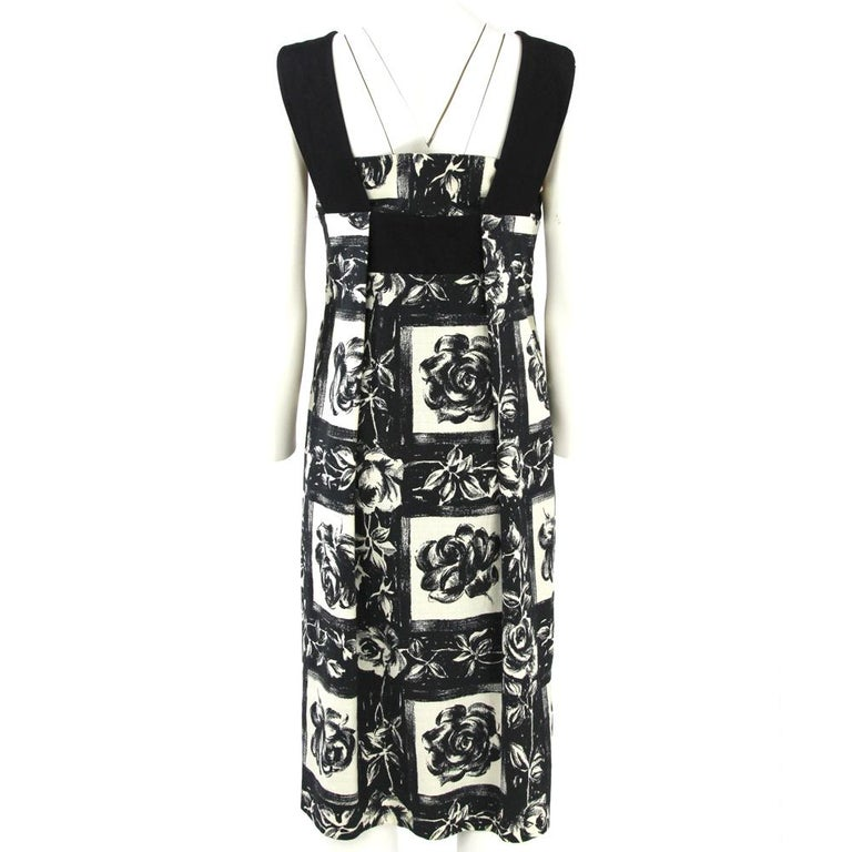 Kenzo midi black and white cotton and linen blend sleeveless dress with a feminine roses printed pattern, wide black straps, black band detail on the upper front and on the back, lightly pleated style and straight hem. Lined in black fabric.  Years:
