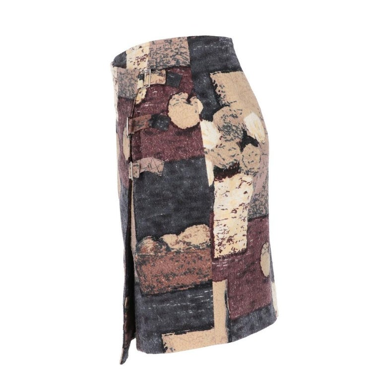 Kenzo wool blend skirt with geometric print in shades of blue, beige, burgundy and brown. Wrap closure with straps, buckles and hidden button.   Years: 2000s   Made in Italy   Size: 36 FR    Flat measurements:  Height: 46 cm  Waist: 34 cm