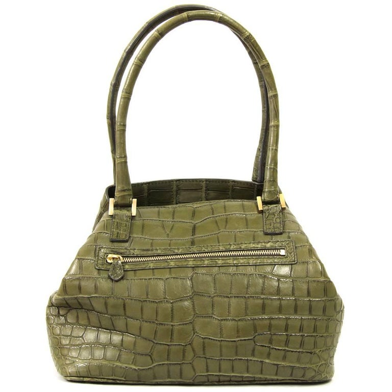 Such a luxurious, stunning handbag by Italian brand Loro Piana. This piece is made of luscious military green crocodile leather and golden hardware, with super soft caramel leather lining and press lock. Features a zip pocket on the back and one