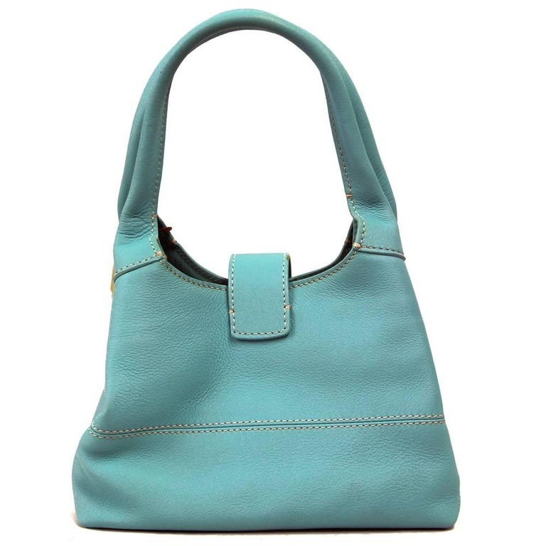Very classy and fashionable Loro Piana purse from the 2000s. This very high quality item in a vibrant turquoise colour features one zip pocket in the inside. Closes with one press stud closure and by entering the upper strip in the designated