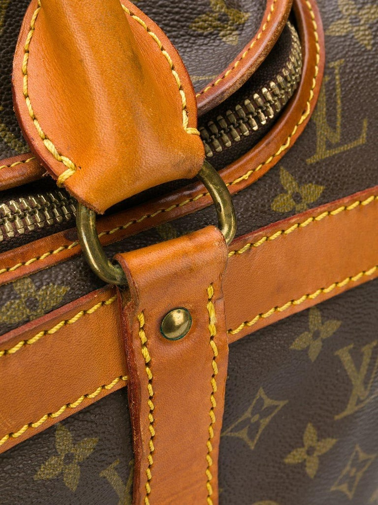 Brown leather monogram travel bag from Louis Vuitton Vintage featuring a monogram print, a structured design, a rectangular body, round top handles, leather trims, a hanging luggage tag, stitching details, a foldover top, an all around zip fastening