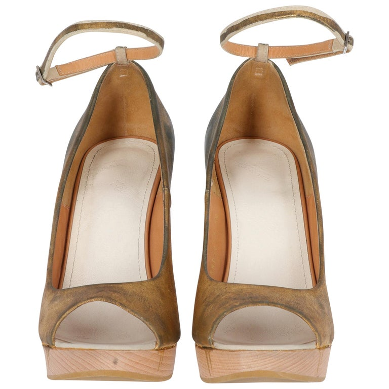 Maison Martin Margiela shoes, in golden leather, beige wooden heel, open toe and adjustable ankle strap. It comes with its original box.  This model is treated on finished garment according to the artistic traditional technique of gilding. On each