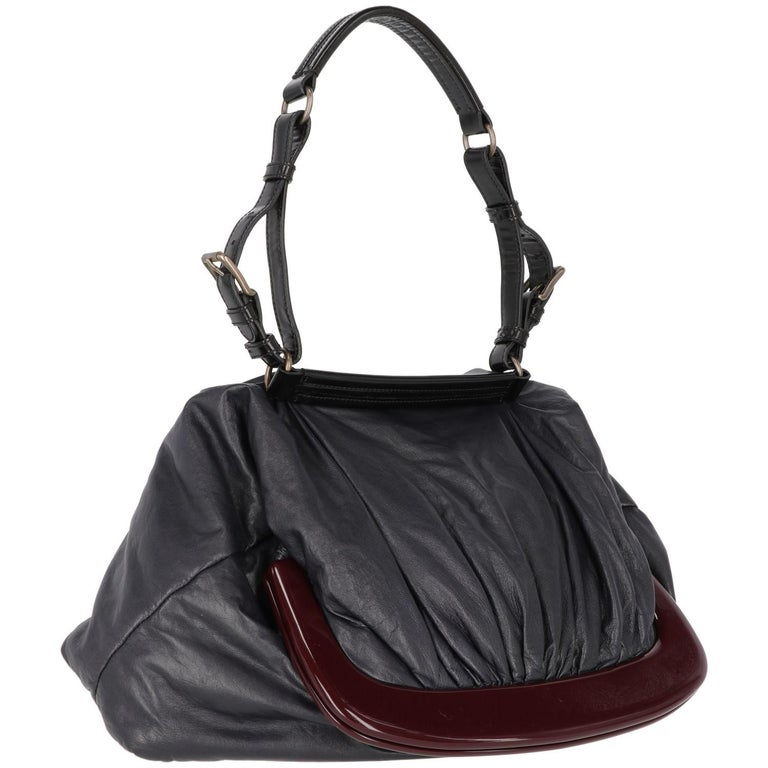 The original Marni blue nappa leather design tote bag  features a black leather handle and a bordeaux pvc clasp closure.  The item shows scratches, as shown in the pictures.  Years: 2000s  Made in Italy  Width: 28 cm Height: 44 cm Handle: 57 cm