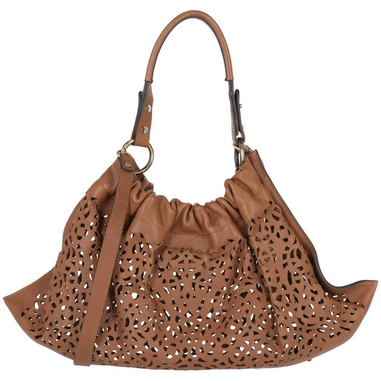 This Marni brown cutout leather bag comes with a detachable and adjustable shoulder strap, the handle is  embellished by gold-tone metal buckles and branded details. At top, the snap button closure.  Years: 2000s  Made in Italy  Width: 53 cm Height: