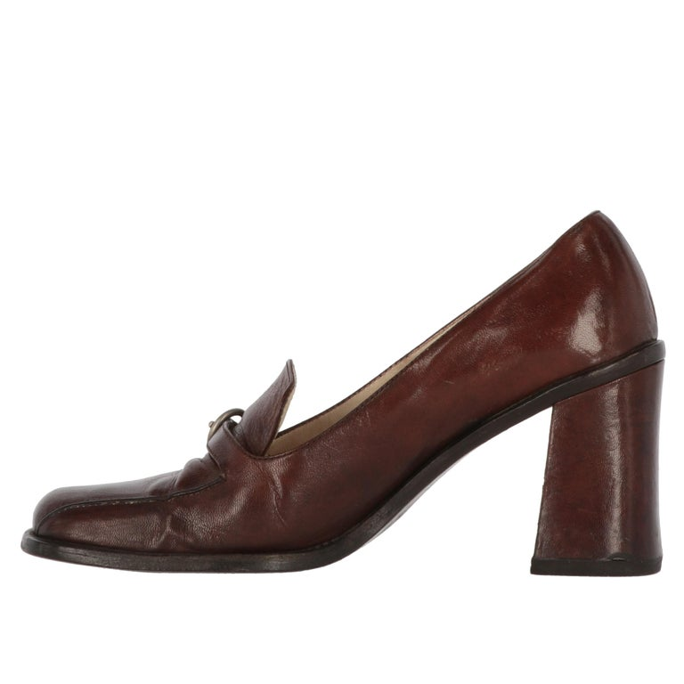Brown genuine leather heeled loafers with strap and buckle, a sophisticated piece by Miu Miu. Square toe and chunky heel. The shoes show signs of wear and wrinkles on the leather, and a halo on the as shown in the pictures.  Years: 2000s  Made in