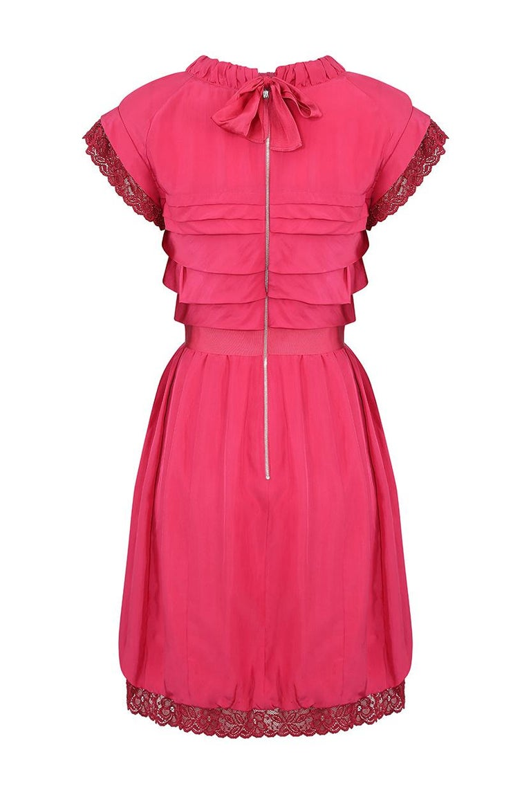 This 2000's deep pink silk pleated dress is by the celebrated French fashion house Nina Ricci and is beautifully constructed and in exceptional condition.  This has all the hallmarks of an Olivier Theyskens design, the vibrant raspberry toned silk