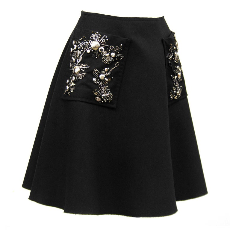 Prada black wool high waisted full A-line skirt from the early 2000's. Large patch pockets with classic silver and black Prada beaded embellishment and raw hem. Invisible zipper up centre back seam. Perfect with a black turtleneck, black tights and