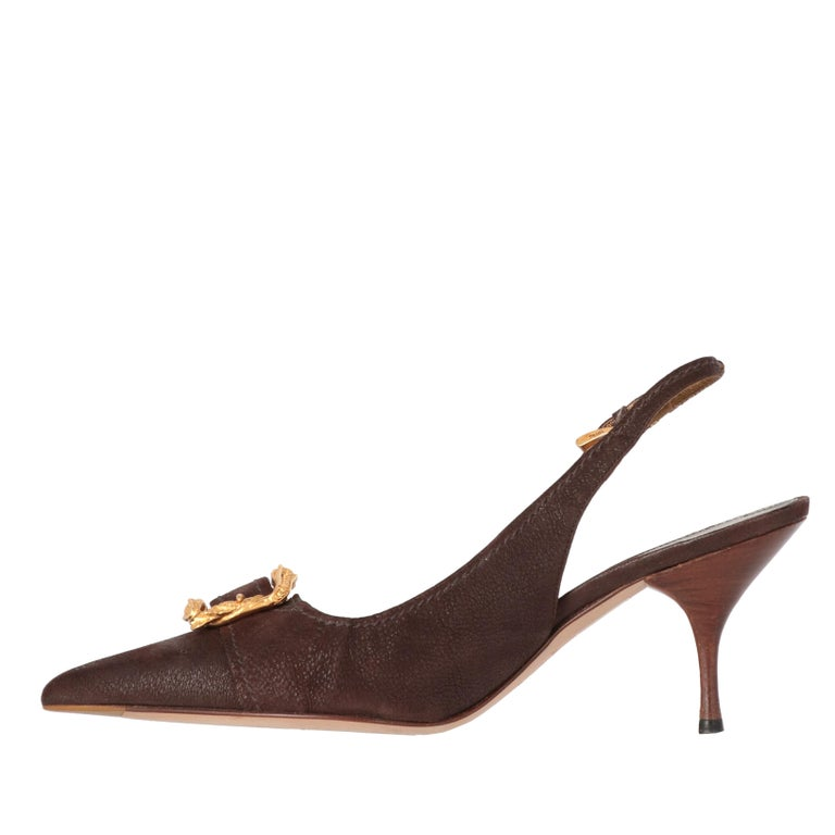 Prada brown genuine leather heeled slingback shoes with pointed toe, ankle strap and logoed gold-tone small buckle. Featuring a decorative strap on the toe cap and gold-tone metal jewel buckle in the shape of two Ouroboros-style snakes with floral