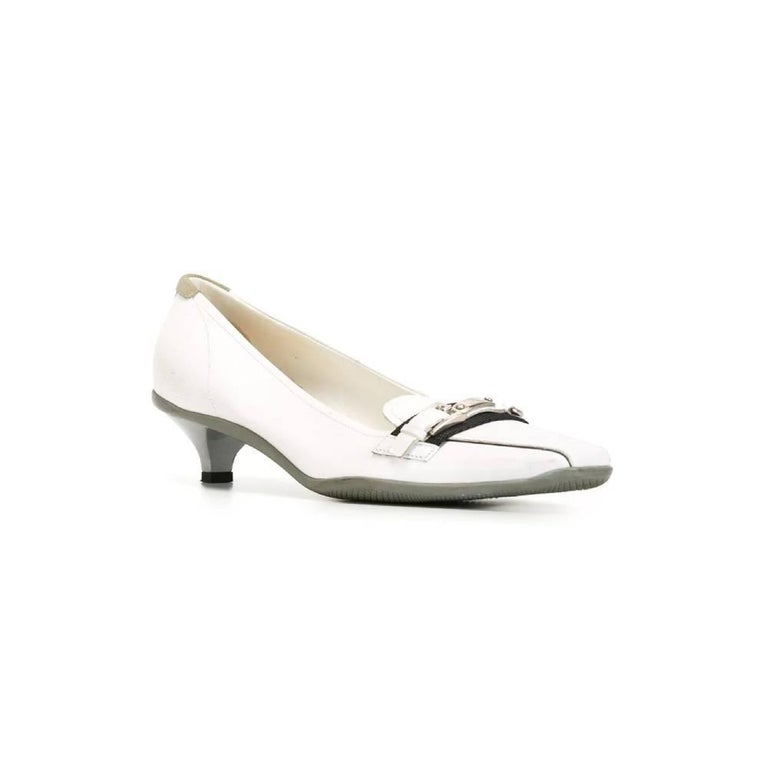 Prada kitten heels pumps in white leather with square toe, front buckle in leather and silver metal, insole in white leather with logo and low heel. The item shows a stain and signs of wear, as shows in the pictures. Years: 2000s  Made in