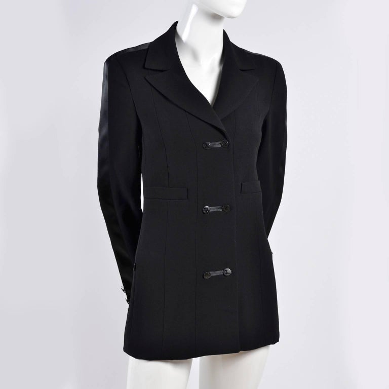 This is a beautiful Chanel Autumn 2003 black wool blazer with double breasted cc Logo buttons up the front,  decorative pockets and functional slit zip front pockets.  There is a wide satin stripe of fabric on each sleeve that runs up the shoulders