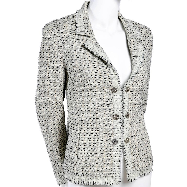 This Chanel jacket is from 2004 and is in a black, ivory and cream Lessage fantasy tweed made of 49% cotton 25% wool 11% nylon 10% Rayon and 5% linen. This short blazer has logo pale ecru silk lining, slit pockets, double chain front cc logo buttons