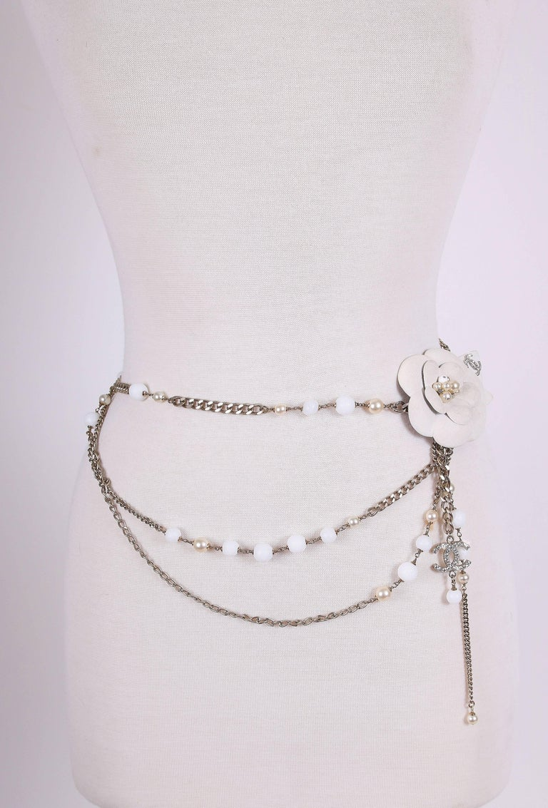 Chanel 2005-2006 A/H belt made from a variety of silver tone curb chain, beads, hanging crystal CC logo charm and textured metal Camellia w/CC logo and pearls at center. In excellent condition. MEASUREMENTS: Length - approx. 33