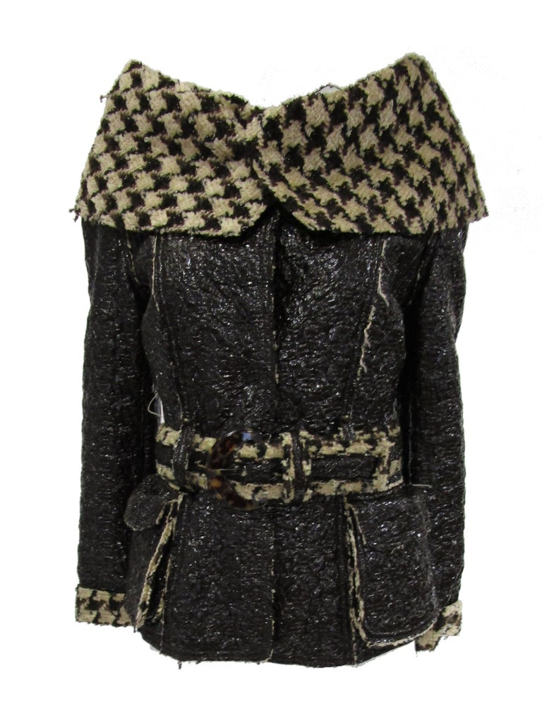 Delightful and unexpected jacket by Oscar de la Renta. This hip - length black coat features a glossy crackle coated brown fabric that is accented by a bold but supple houndstooth print on the collar. The collar is something else! It folds over the