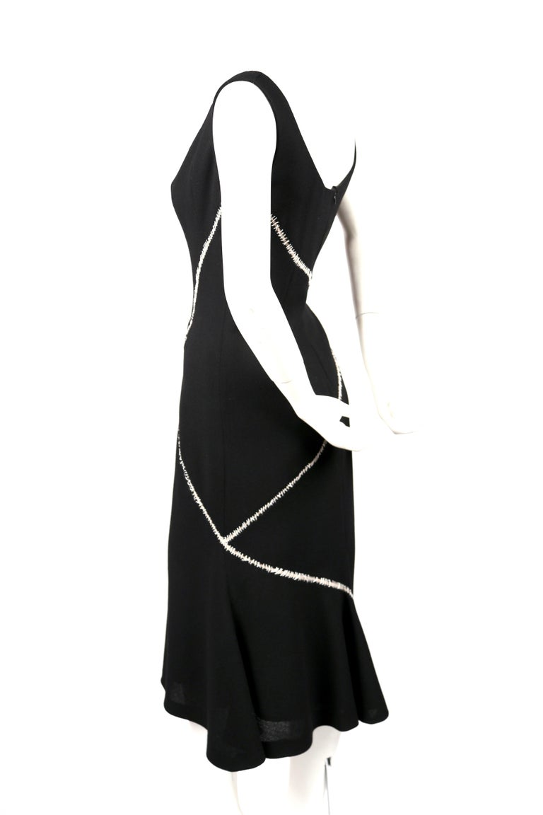 Black wool and silk crepe dress with decorative white stitched detail designed by Alexander McQueen circa 2008. Labeled an Italian size 42. Measures approximately: 34