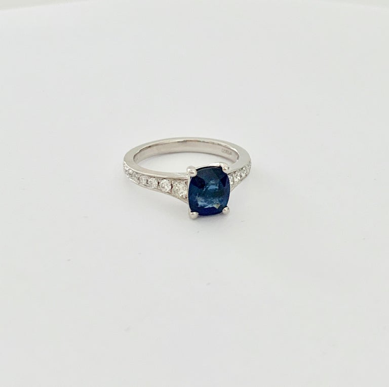 This rich velvet blue cushion cut *Sapphire is set in an elegant platinum band. this band has an outward taper towards the Sapphire and is set each side with 7 graduating diamonds totalling 0.24ct.  The band also has a very delicate milgrain finish.