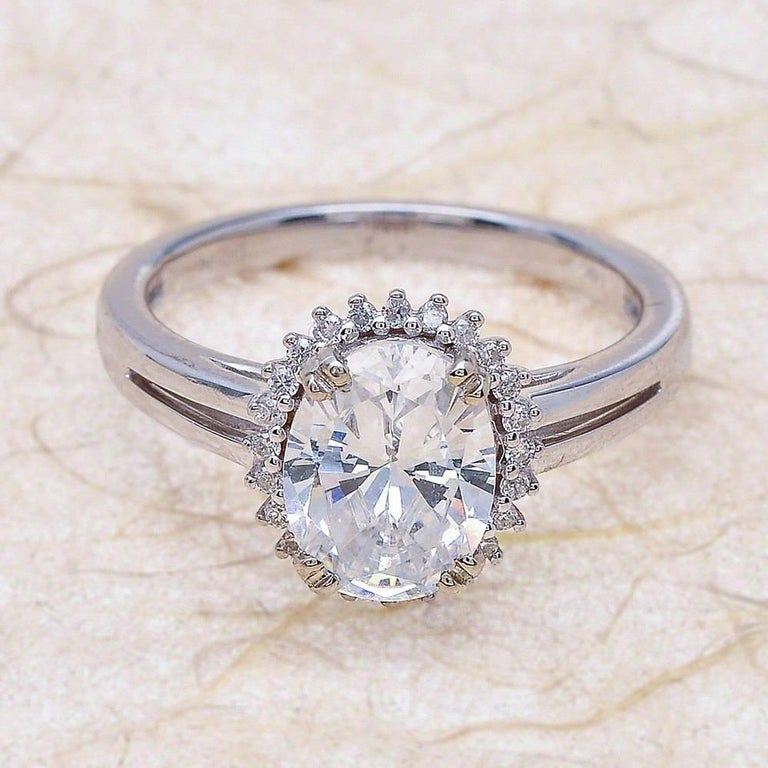 - Center Stone: Oval Cut Moissanite 9x7mm (2.00ct) - Side Stones: Round Cut Diamonds 0.30ctw / Graded G SI1 - Metal: 14K White Gold  This piece is made-to-order. Please allow up to 7 Business Days to accomplish.