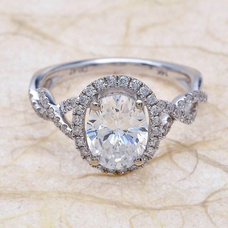 - Center Stone: Oval Cut Moissanite 9x7mm (2.00ct) - Side Stones: Round Cut Diamonds 0.50ctw / Graded G SI1 - Metal: 14K White Gold  This piece is made-to-order. Please allow up to 7 Business Days to accomplish.