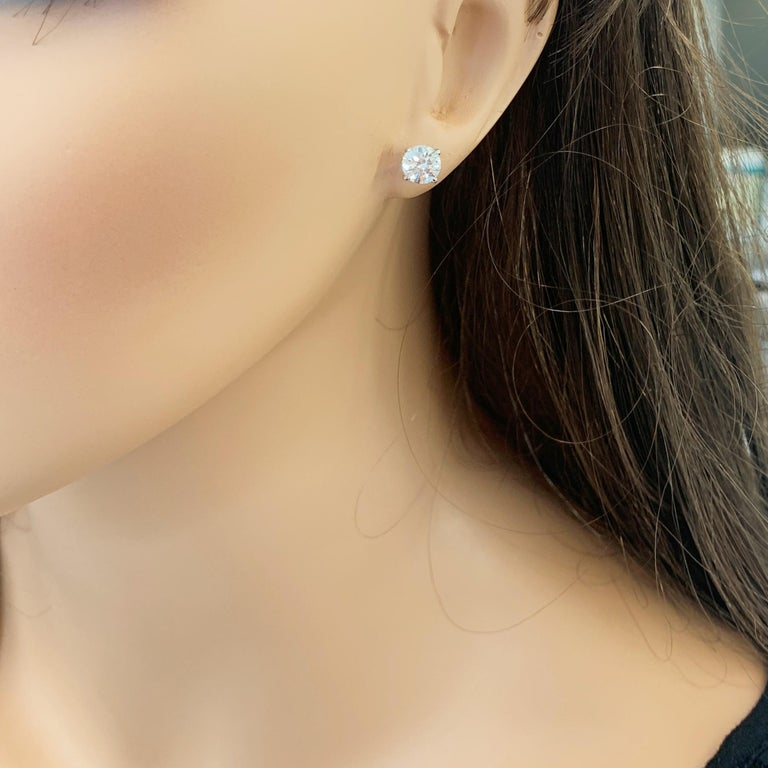 Stunning 14 Karat white gold handmade earrings featuring 2 round brilliant cut diamonds weighing 2.01 carat total J color VS2 clarity. The stunning earrings measure 6.25 - 6.31 mm in diameter, these gorgeous earrings are classic and timelessly