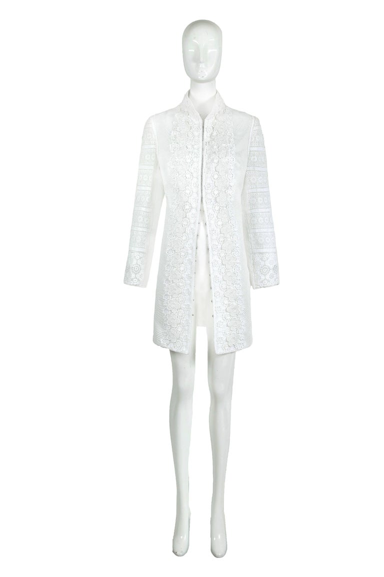 2010 Andrew Gn Atelier white cotton blend jacket coat with embroidered lace and floral appliqués down center front as well as lace embroidered sleeves. Metal hook and eye closure. Interior lining at body of coat and sleeves. In excellent condition.
