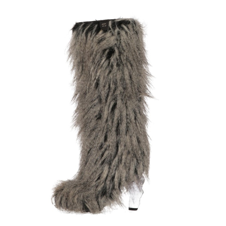 Chanel grey and black faux fur boots, with hidden side zip and the one of a kind transparent plexiglass icicle heel. They features a black genuine leather label with silver-tone metal CC iconic logo on the top. Leather edging and lining.  The right