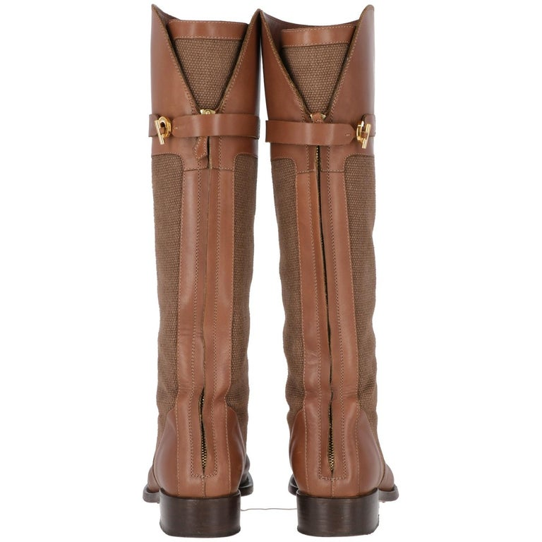 The stylish Loro Piana high brown leather boots feature brown fabric inserts and round toes. Boots are embellished by golden back fastening and golden branded metal buckles details.  Original box and dust-bags are included. The item shows some