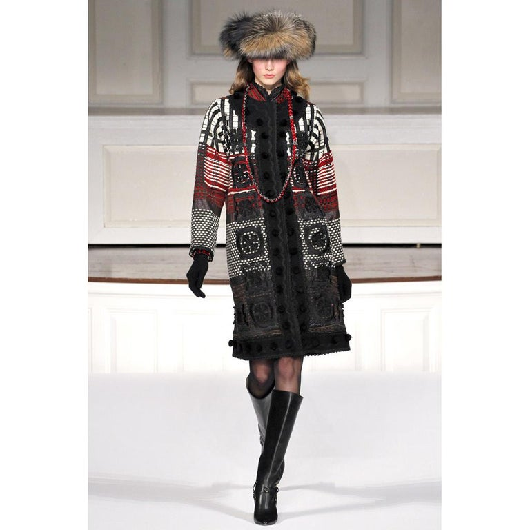 This is a wonderful Oscar de la Renta coat in black white and red with wool pom poms. This incredible tweed coat has side slit pockets, wool boucle trim, an interesting mixed pattern and soutache trim. We love this particular piece and estimate it