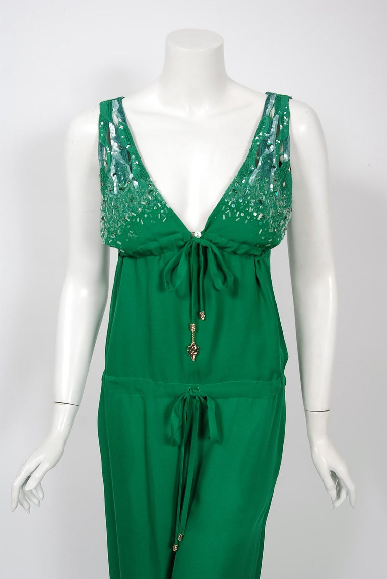 This gorgeous 2011 creation from Roberto Cavalli is not only striking but shockingly timeless. The fabric is luxurious emerald green high-quality silk upon which glass-beads and jewels in the matching hue have been worked in so there is a beautiful