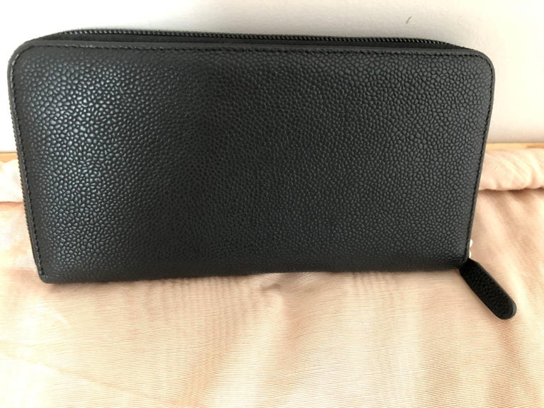 This is a 2012-2013 Chanel Black Caviar Coco Zip Around Long Wallet with a two-tone (beige/black) Chanel button. Made in Italy, it has 8 credit card slots (4 on each side); a zipped middle compartment, and 4 open slots. In as new condition except
