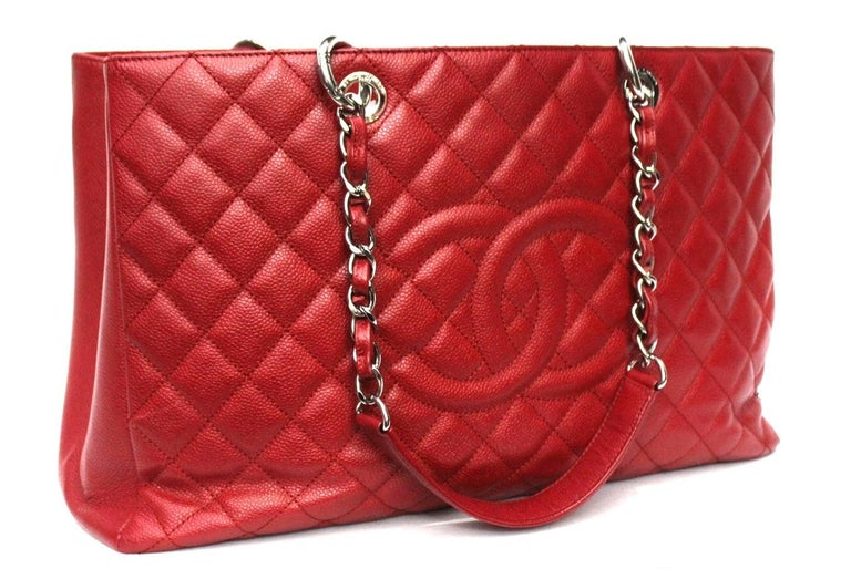 Chanel GST model bag currently out of production.  Made of red textured leather with silver hardware.  Equipped with double leather handle and chain, very large inside.  The bag is in excellent condition.