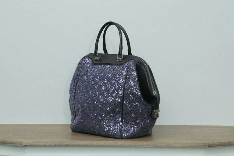 This Louis Vuitton North South Bag Limited Edition Sunshine Express, crafted from purple sequin-embroidered wool with monogram pattern, features dual rolled leather handles, leather trim, and matte silver-tone hardware. Its zip closure with