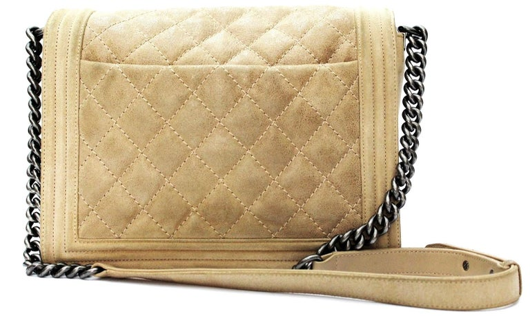 Beautiful Chanel Boy model bag made of beige suede. It is the largest size of the Boy collection and features a long chain strap with a leather mat that can be worn as a shoulder bag or simply shoulder. Excellent conditions.