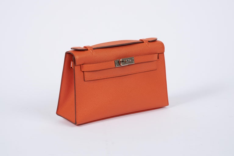 Hermes orange epsom leather Kelly pouchette with palladium hardware. Partial plastic on hardware. Date stamp Q, 2013. Comes with original dust cover.