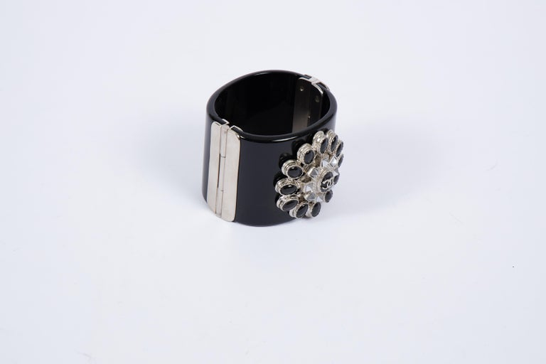 Chanel black lucite cuff bracelet with black silver and hematite center. Autumn 2014 collection. Comes with original duster and box.