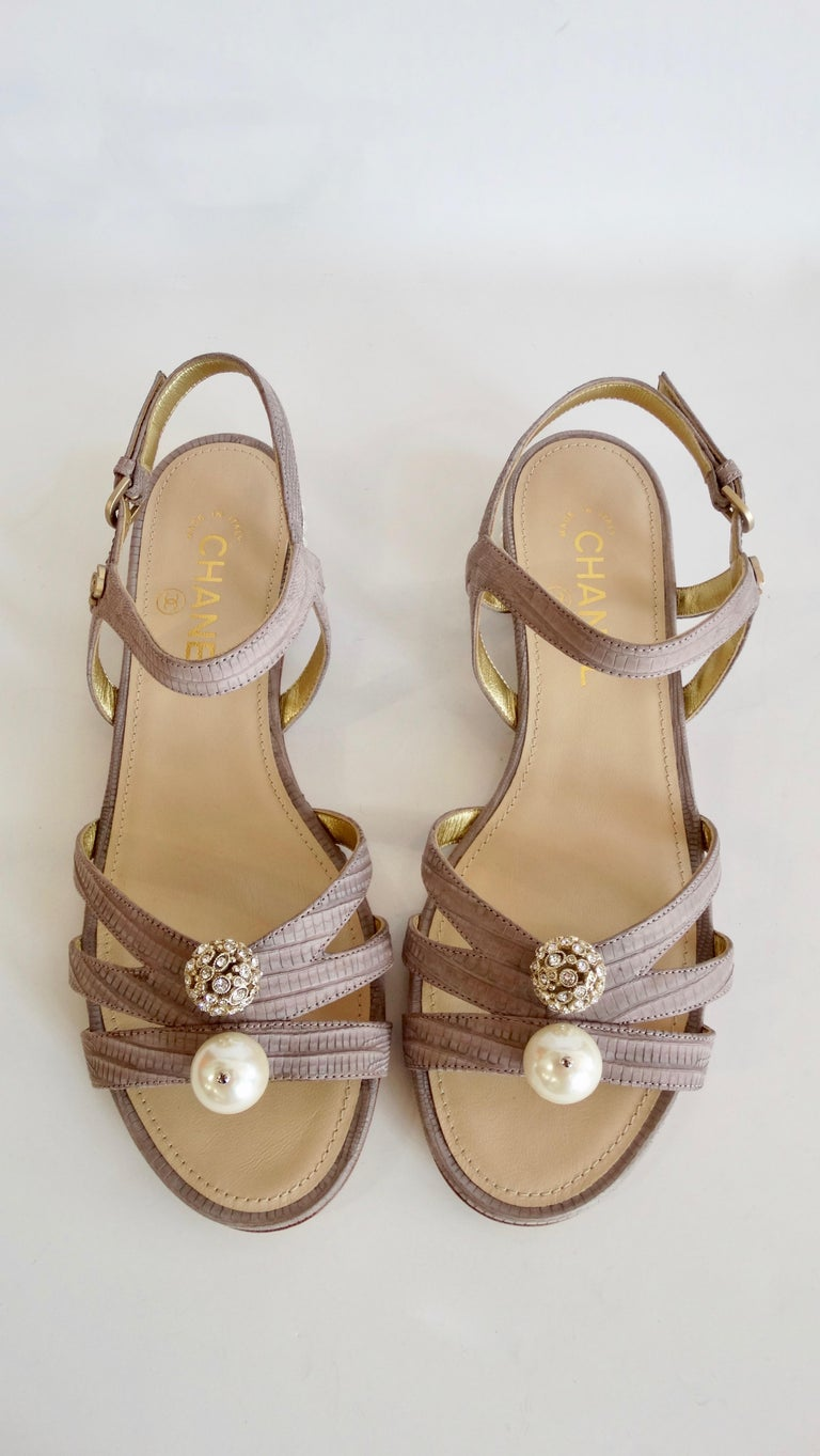 Complete your shoe collection with these chic Chanel sandals! Circa 2015 from their Cruise collection, these strappy sandals are crafted from pastel purple dyed lizard skin and feature a faux pearl studded heel. Front of sandal is adorned with a